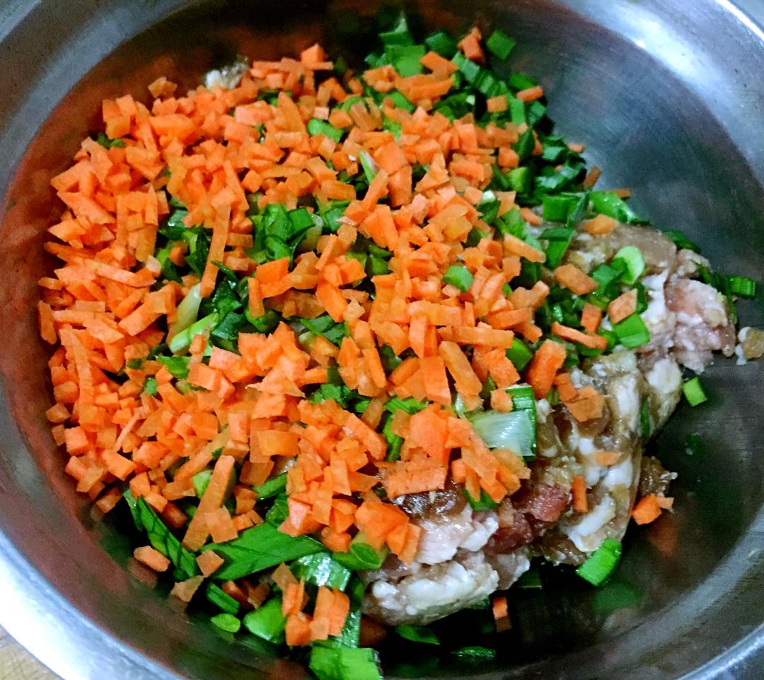 胡萝卜切成碎丁和韭菜一起放入腌制入味的肉馅中