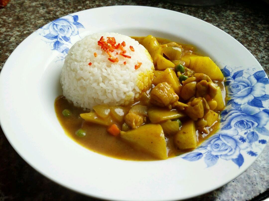 米饭装进碗里用调羹按平倒扣在盘子里,在将咖喱鸡腿土豆装入米饭边