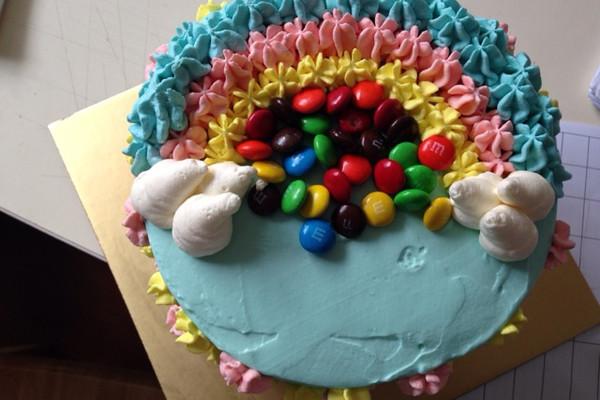 5. 7片蛋糕烤好放凉以后就要打发淡奶油了,将淡奶油和糖倒入盆中。隔冰水打至七分发,分出约200g奶油由于做彩虹用,剩余的500g奶油加少许蓝色素搅拌均匀涂抹于蛋糕表面,用抹刀将蛋糕抹平,剩余的200g奶油分成三分,分别加红、黄、蓝三种色素调匀,装入表花袋在蛋糕上挤成彩虹的样子,最后撒上M豆。好了,大功告成!