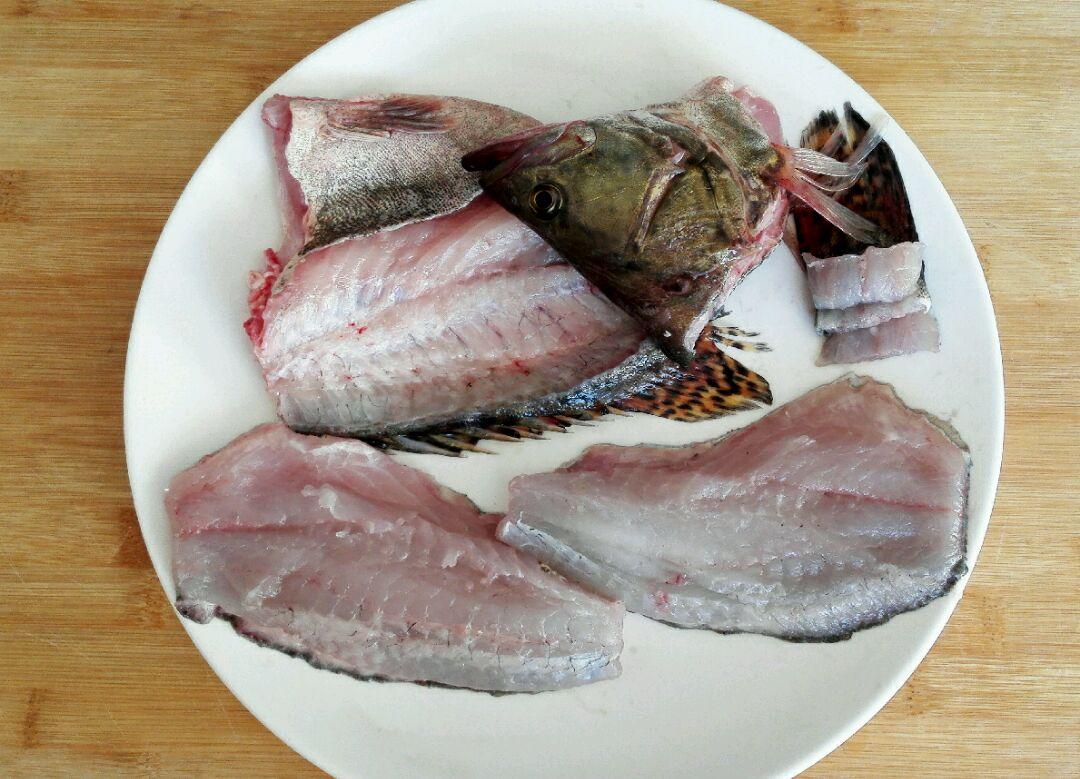 松鼠桂鱼的做法步骤 2. 切下鱼头,从鱼背贴骨片下两块鱼肉.